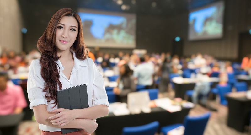 Woman working at a convention with projectors