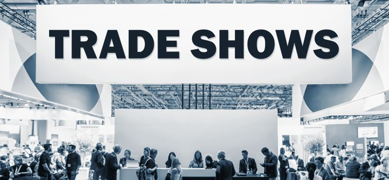 Crowd of people at a trade show booth with a banner and the text Trade Shows.